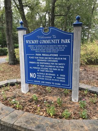 Royal blue sign with the words Wyckoff Community Park listing rules and regulations for park use
