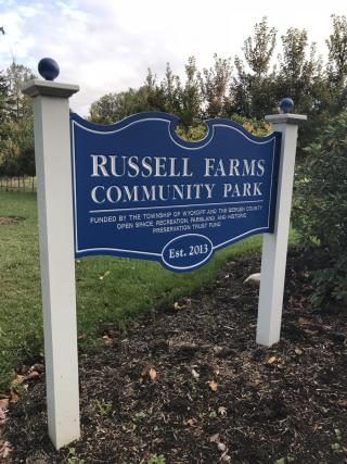 Royal Blue sign with the words Russell Farms Community Park